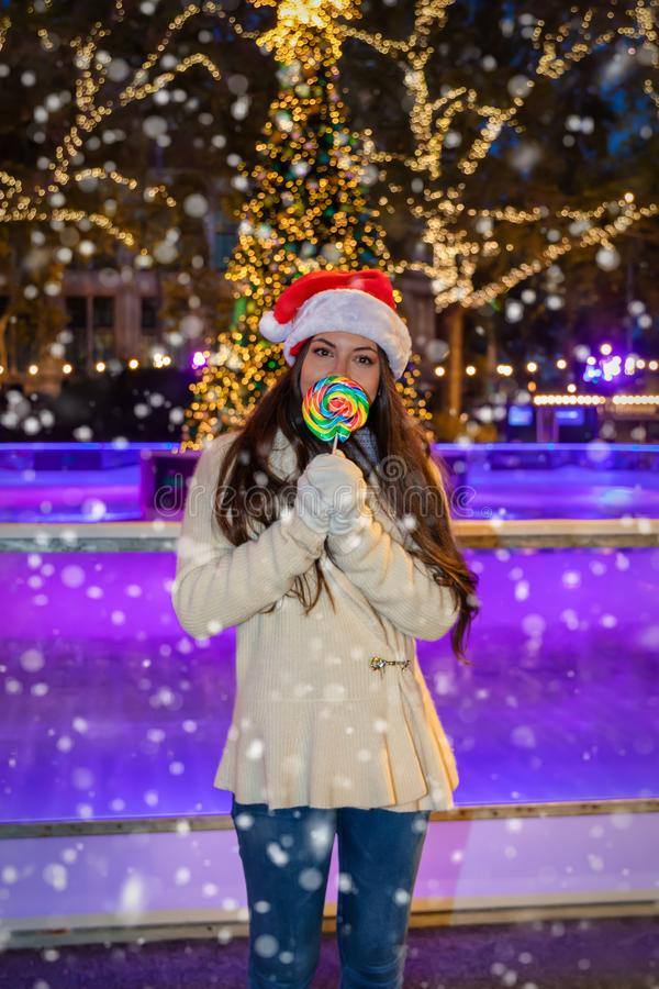 Young woman with a red Santa Claus hat stands next to an ice rink stock image