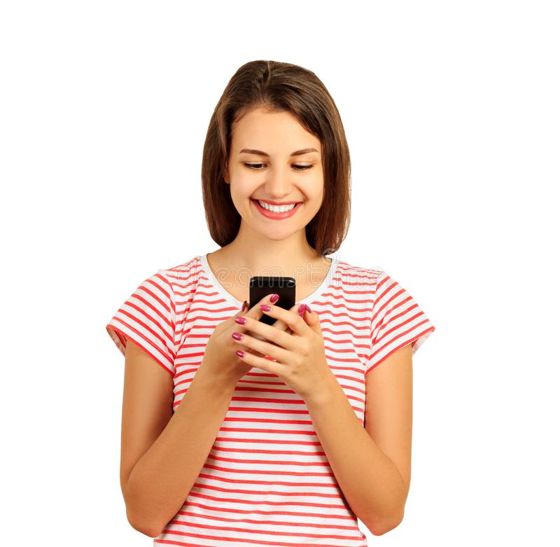 Young woman in a red striped t-shirt looks at the phone and smiles, good news, joy. emotional girl isolated on white background.  stock photography