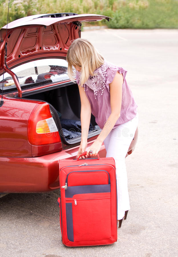 Download Young Woman With A Red Suitcase In The Car Stock Photography - Image: 26614512