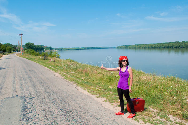 Young woman with a red suitcase hitching a lift royalty free stock photography