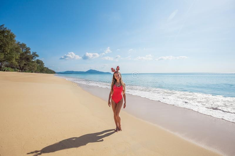 Young woman in red swimsuit wearing funny christmas reindeer ant. Happy young woman with long hair in red swimsuit wearing funny christmas reindeer antlers while stock photos