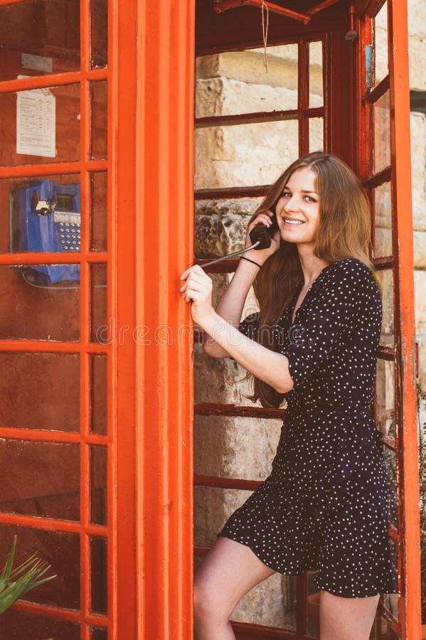 Young woman in telephone cabin talking on the phone and smiling royalty free stock image