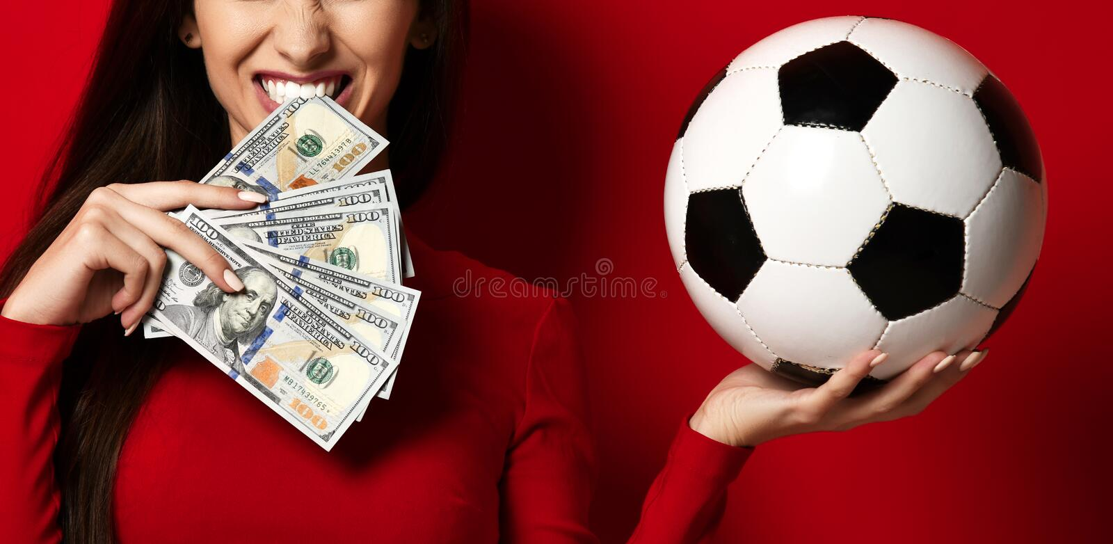 Young woman in red uniform hold soccer ball and dollar money for sports betting celebrating. Happy up with free text copy space on red background royalty free stock photo