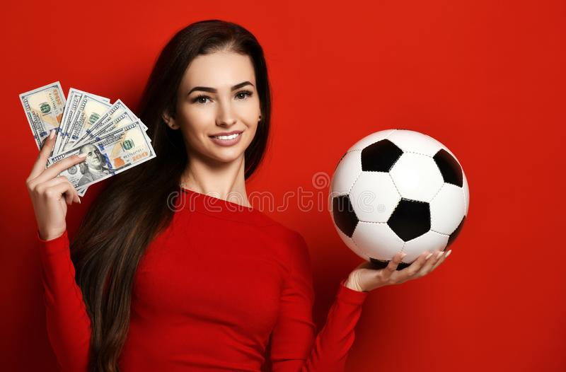Young woman in red uniform hold soccer ball and dollar money for sports betting celebrating. Happy up with free text copy space on red background stock images