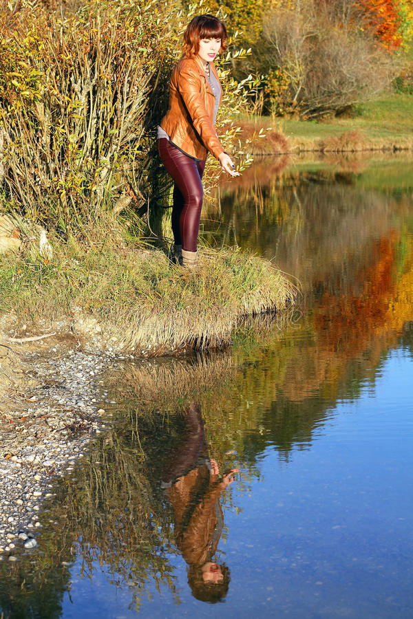 Young woman is reflected in the autumn lake royalty free stock image