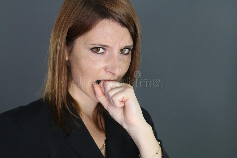 Young woman regretting. Young woman biting his fist on a gray background royalty free stock photography