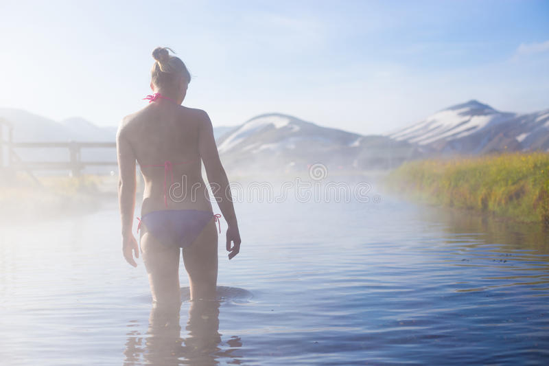 Young woman relax in a hot spring. Iceland Landmannalaugar camping.  stock photo