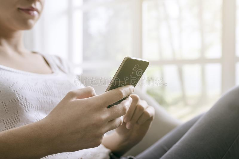 Young woman connecting with her smartphone at home stock photography