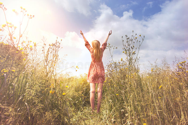 Young woman relaxing with arms raised to the sky in the middle of the nature stock images