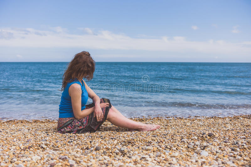 Young woman relaxing on the beach. A young woman is relaxing on the beach in the summer stock photos