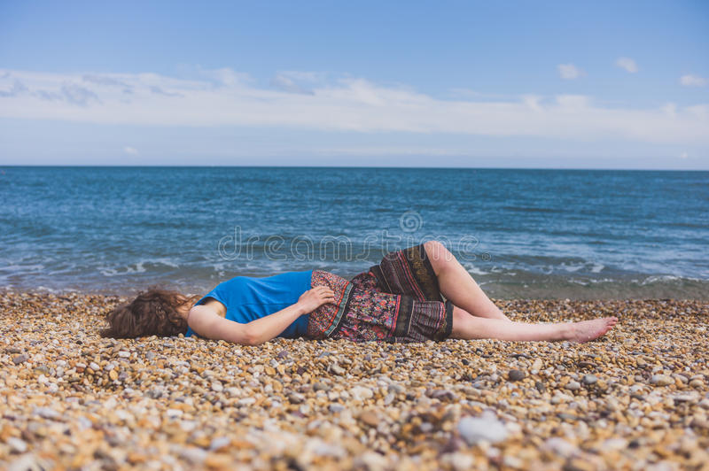 Young woman relaxing on the beach. A young woman is relaxing on the beach in the summer stock photo