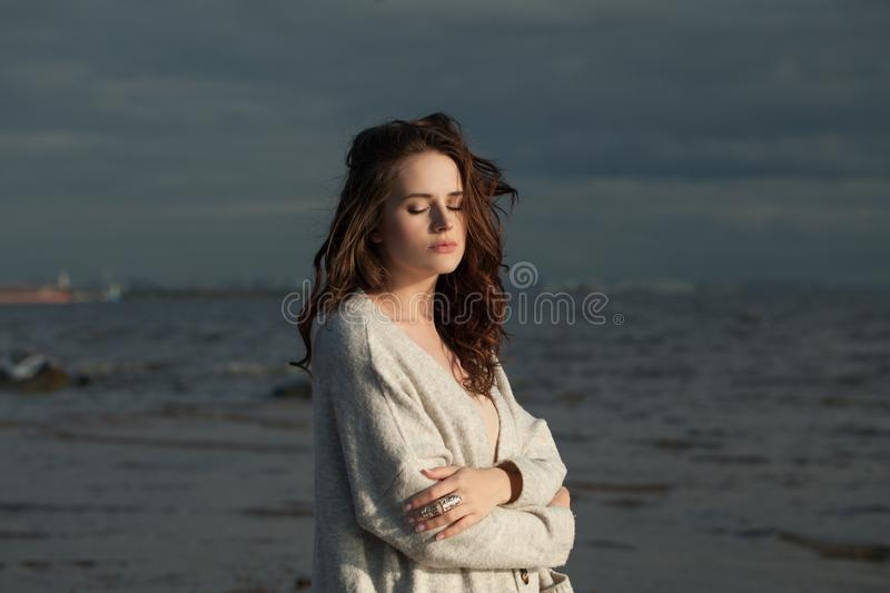 Young woman relaxing on the coastline of the sea. Beauty girl portrait.  royalty free stock photography