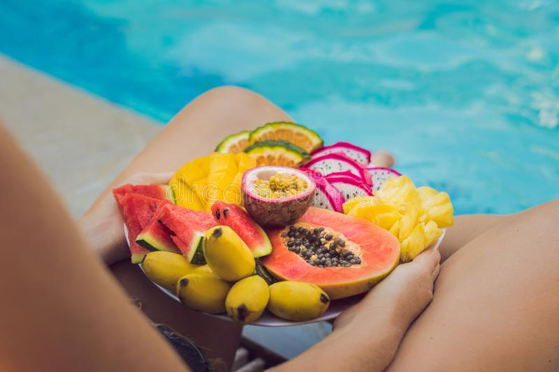 Young woman relaxing and eating fruit plate by the hotel pool. Exotic summer diet. Photo of legs with healthy food by. The poolside, top view from above stock photos