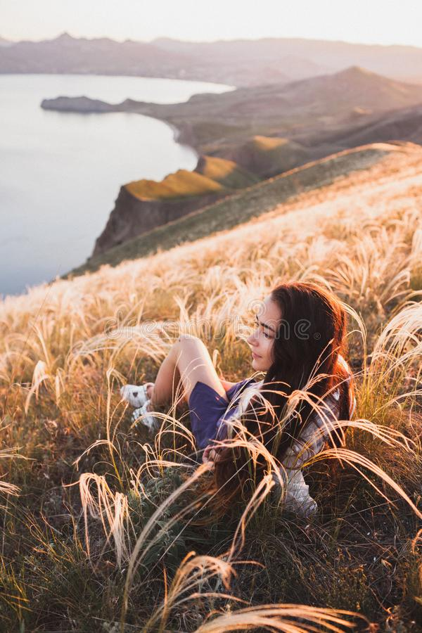Young woman relaxing in grass field at sunset view mountain and sea coast. Young woman relaxing in feather grass field at sunset. Enjoying beautiful mountain stock image