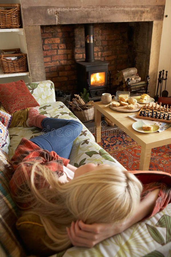 Young woman relaxing by fire stock photos
