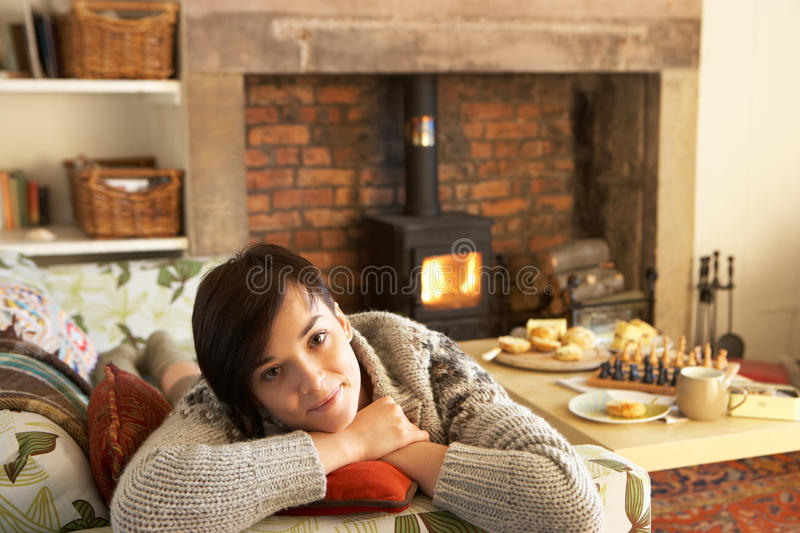 Young woman relaxing by fire royalty free stock images