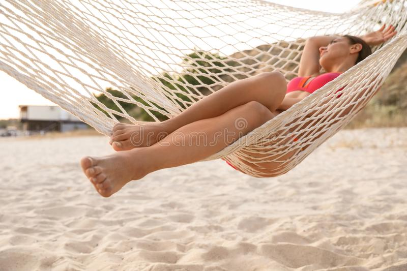Young woman relaxing in hammock on beach. Focus on legs stock images