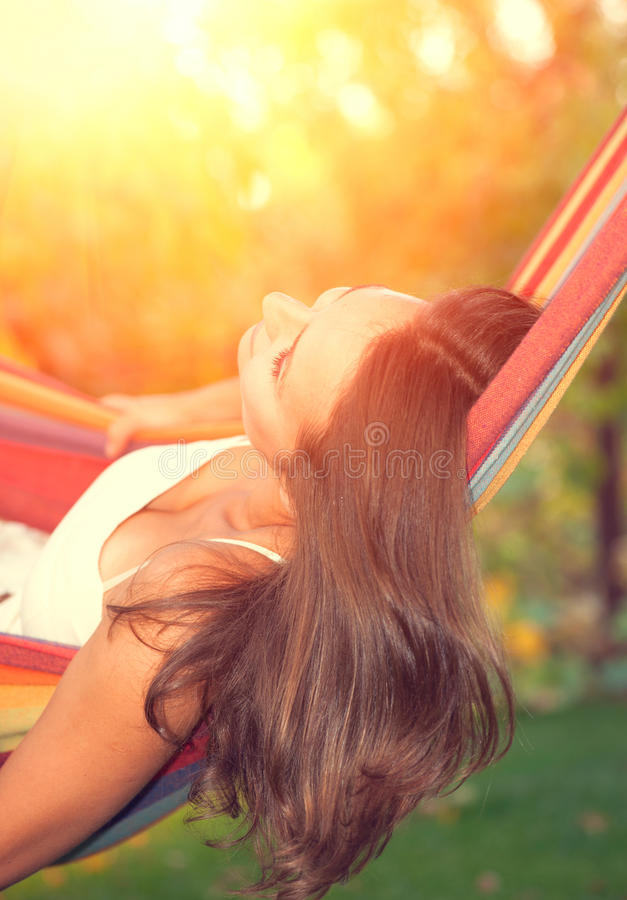 Young woman relaxing in hammock. Beautiful young woman relaxing in hammock stock image