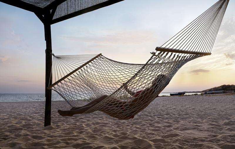 Young woman relaxing in hammock. On beach royalty free stock photography