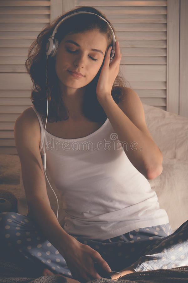 Young woman relaxing in her bed, she is listening to music royalty free stock images