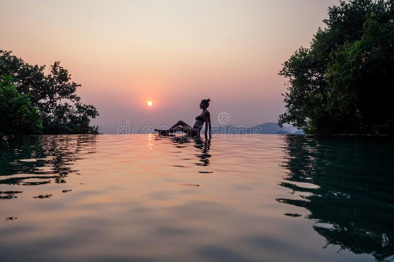 Young woman relaxing in infinity swimming pool looking at view romantic sunset overlooking the hills wildernest nature stock photos