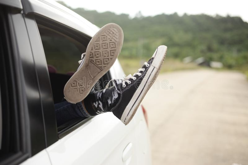 Lazy Feet Outside Car Window. Young woman relaxing and lying during car trip, lazy feet with shoes out of car window summer travel outside girl vacation freedom royalty free stock photography