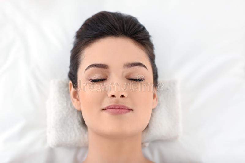 Young woman relaxing on massage table at spa salon, top view stock photography
