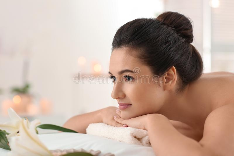 Young woman relaxing on massage table at spa salon royalty free stock images