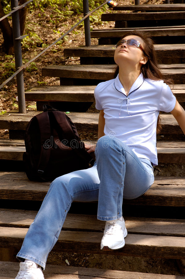 Young woman relaxing in nature summer. Girl sitting on stairs relaxing royalty free stock photos