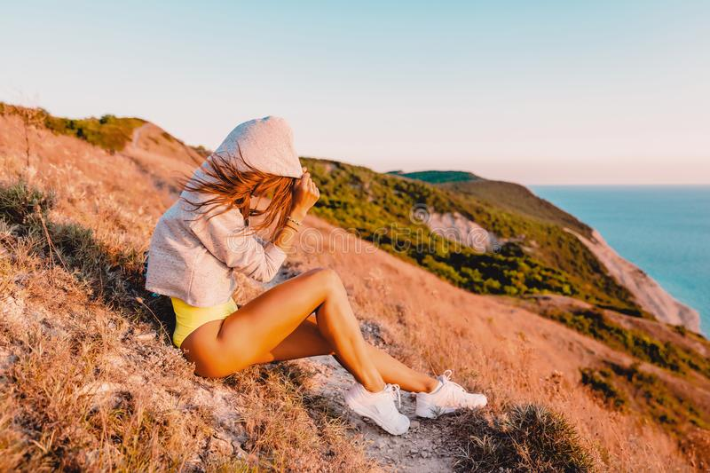 Young woman relaxing in nature at warm sunset. Fitness girl in the mountains. Young woman relaxing in nature at warm sunset. Fitness girl in mountains stock photos