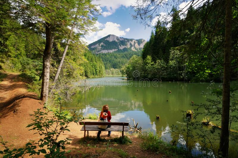 Young woman relaxing near a lake and admiring the landscape. Young woman relaxing near a beautiful lake and admiring the landscape royalty free stock photography