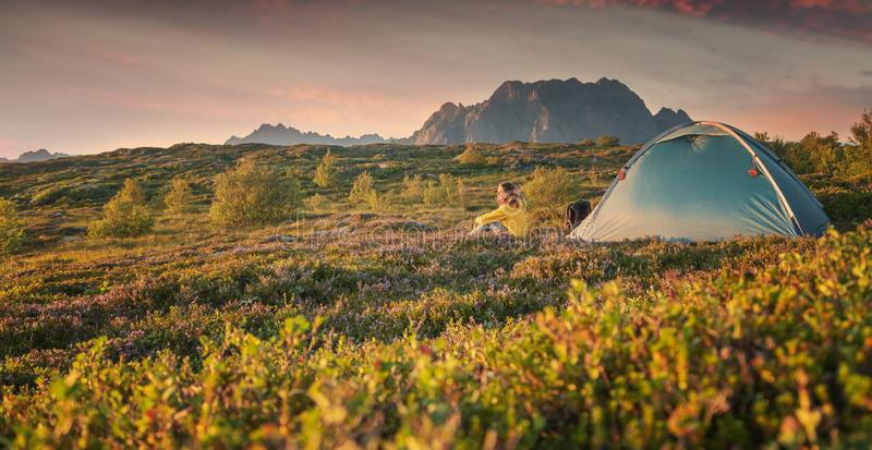 A young woman is relaxing next to a tent on the Lfoten Islands in Norway with views of the sunset and mountains, enjoying the view royalty free stock images