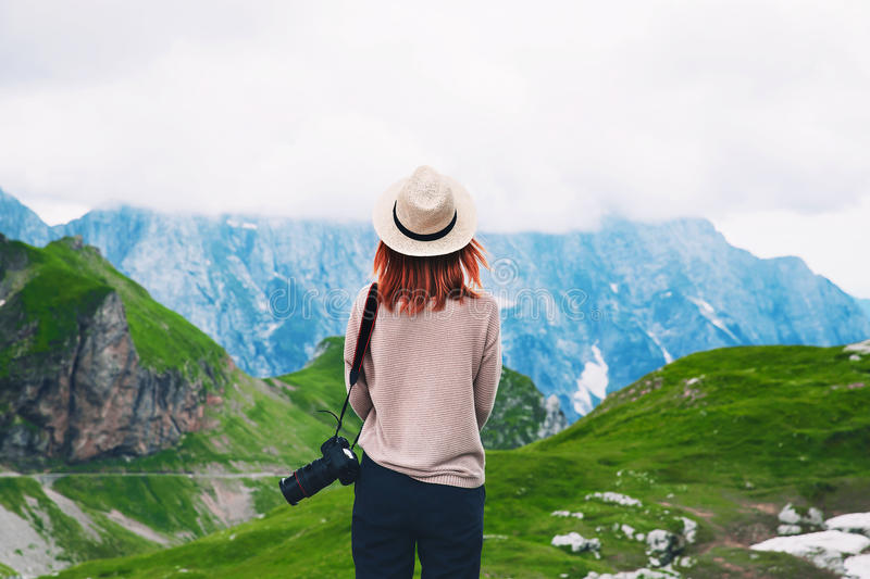 Young woman relaxing outdoor travel freedom lifestyle with mount. Ains on background. Fashionable girl in the Mangart is a mountain in the Julian Alps, located stock image