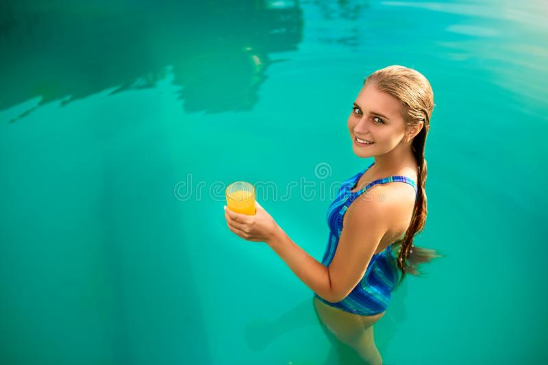 Young woman relaxing in a pool in summer with glass of orange juice. Pretty caucasian blonde girl wearing blue swimsuit stock photos