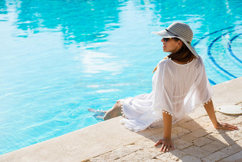 Young woman relaxing at poolside on summer vacation royalty free stock photos