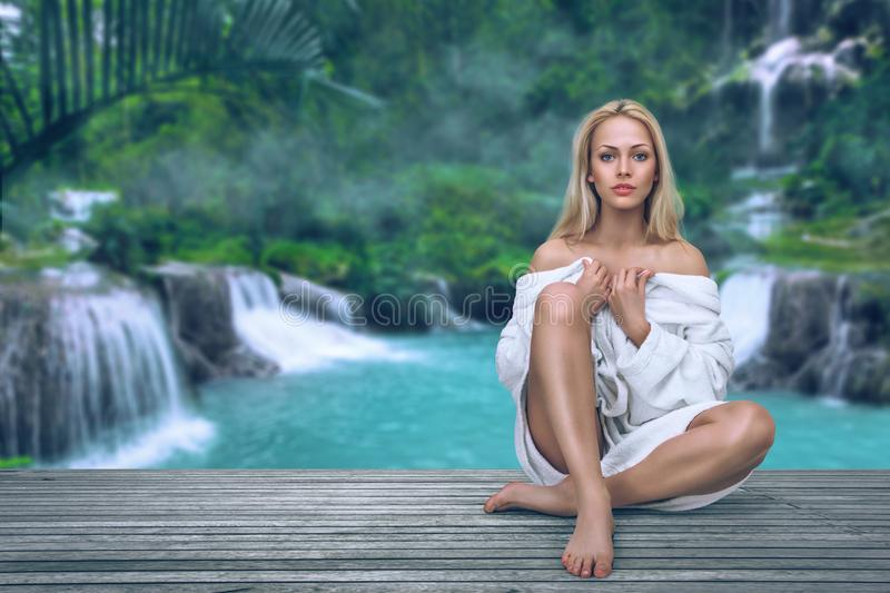 Young woman relaxing in resort spa. In front of waterfall in tropical jungle stock image
