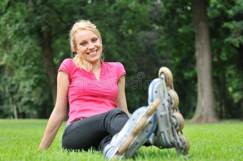Young woman relaxing after roller blading. Young smiling woman relaxing in green grass after roller blading stock photo