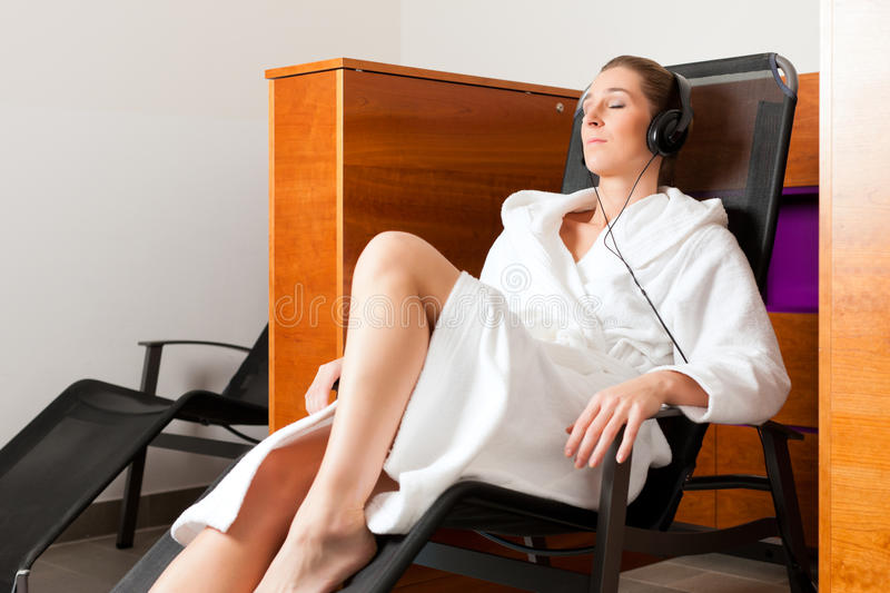 Young woman relaxing in spa with music. Young woman relaxing in spa hearing music with headset in quiet room stock photo