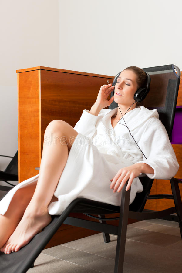 Young woman relaxing in spa with music. Young woman relaxing in spa hearing music with headset in quiet room royalty free stock images