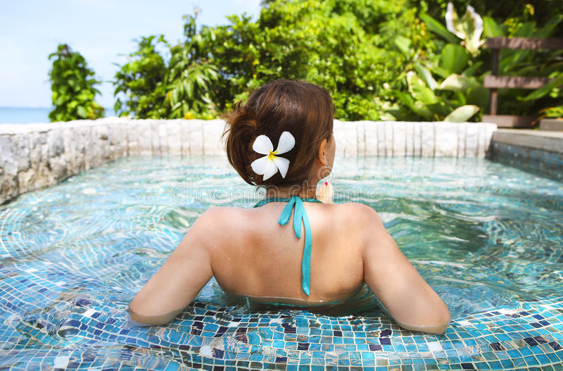 Young woman relaxing in spa pool. Young beautiful woman relaxing in spa pool. Relaxing serene woman at travel spa resort pool stock photography