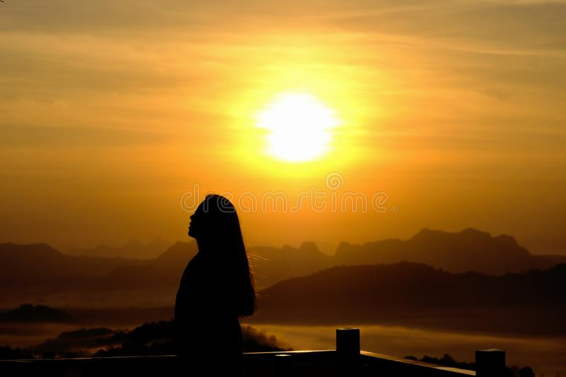 Young woman relaxing in summer sunrise or sunset sky outdoor people girl freedom style on mountain hill background - silhouette royalty free stock photos