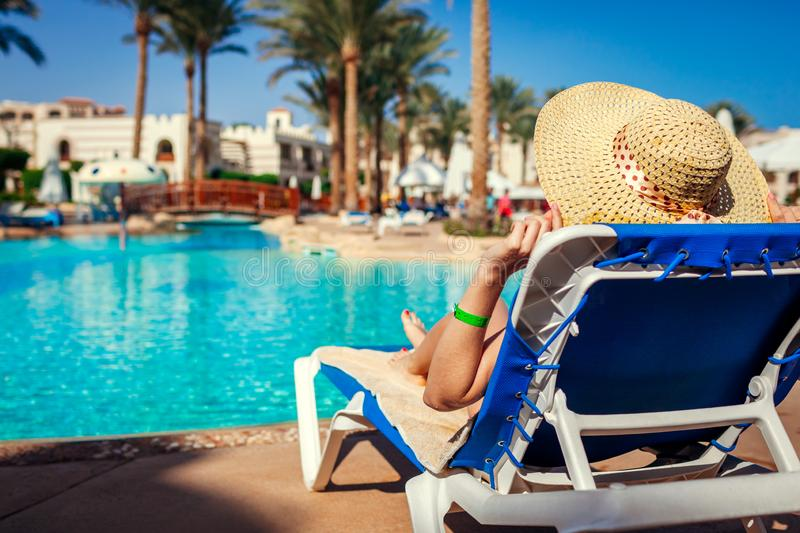 Woman relaxing by swimming pool lying on chaise-longue. Summer vacation. All inclusive royalty free stock photography