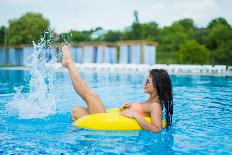 Young beautiful woman is relaxing in swimming pool with rubber ring. Young woman is relaxing in swimming pool with rubber ring stock photography