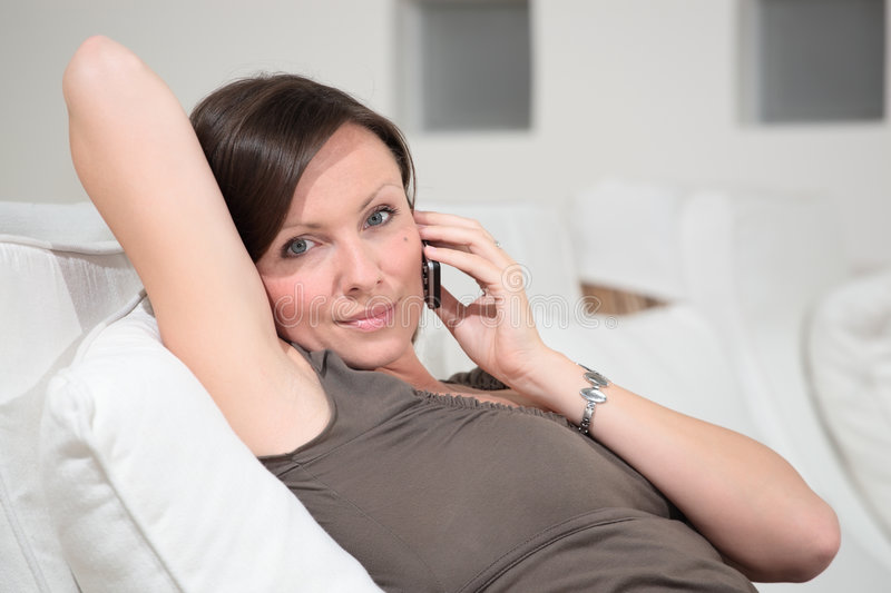 Young woman relaxing talking on the pho. Young beautiful woman relaxing talking on the phone royalty free stock images