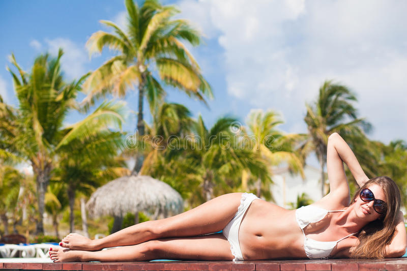 Young woman relaxing by the tropical pool royalty free stock photo