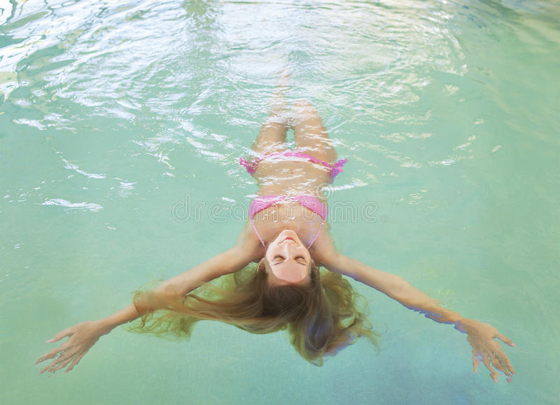 Young woman relaxing in the water. Young blond woman relaxing in the water in the pool royalty free stock images