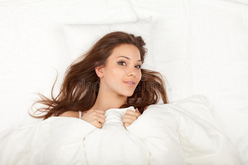 Download Young Woman Relaxing In White Bedding Stock Image - Image of indoors, girl: 18606367