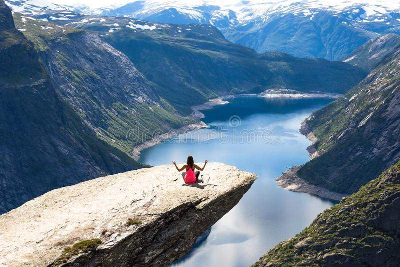 Young woman relaxon Trolltunga. Happy girl enjoy beautiful lake and good weather in Norway. stock photography