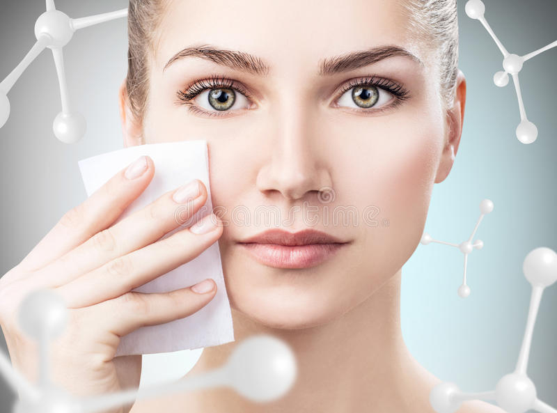 Young woman remove makeup among molecules. Beautiful young woman remove makeup among molecules over gray background. Innovation cosmetics concept stock image