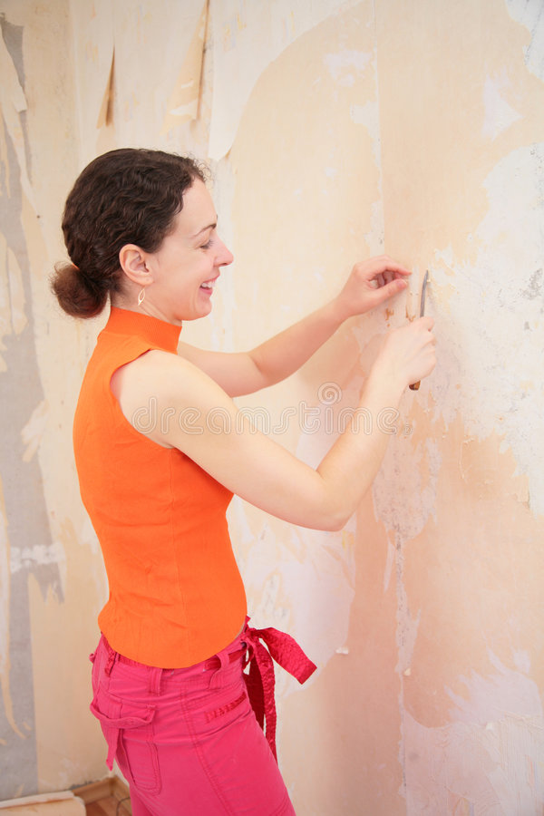 Young woman remove old wallpapers royalty free stock images